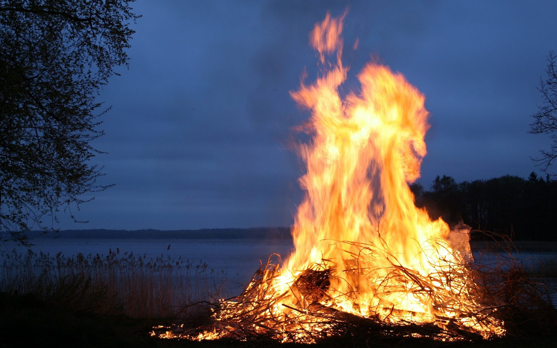 bonfire by a lake at dusk