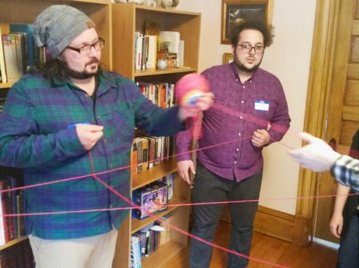 a circle of people passing a ball of yarn