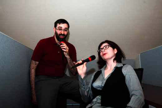 man and woman in a cubicle singing into microphones