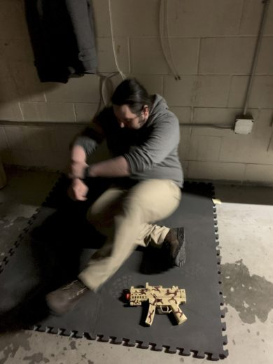 Man on a mat with a gun