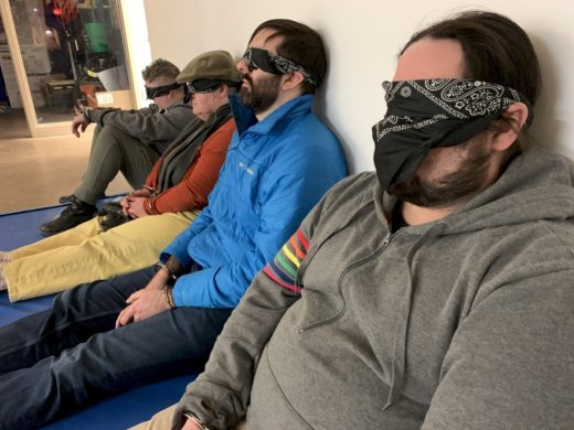 row of people against a wall blindfolded