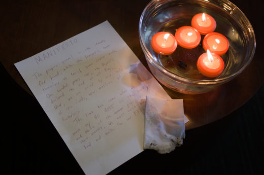 handwritten document titled MANIFESTO, burned letter, and bowl of water with floating candles