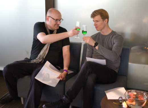 two people toasting with green drinks