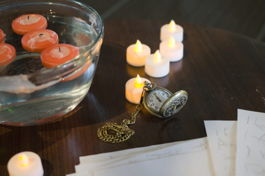 pocketwatch on table with electric candles and candles in bowl of water