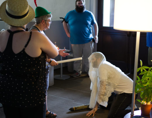 person with rolled map standing over kneeling person in veil