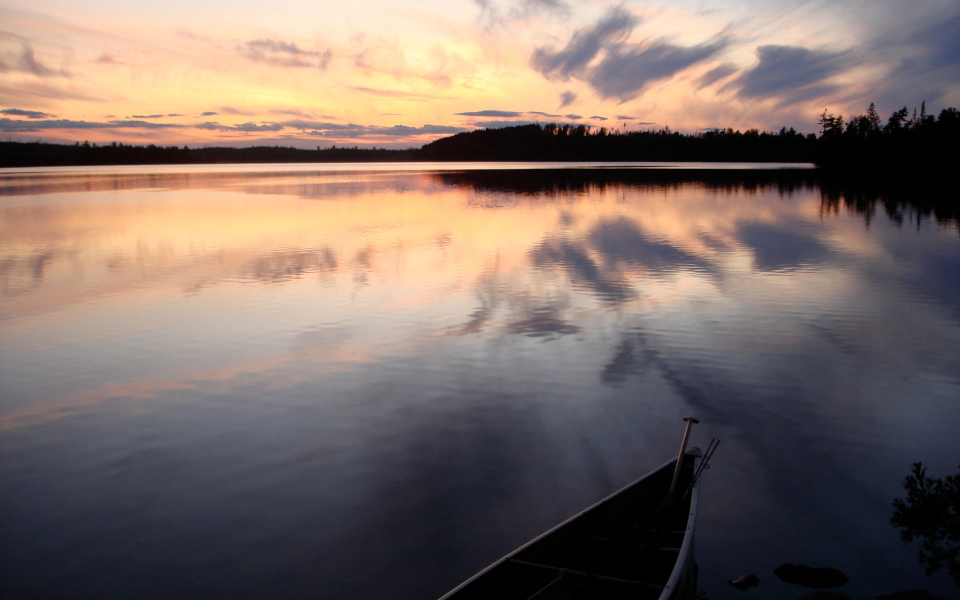 Sunset over a wooded lake with a canoe in the foreground