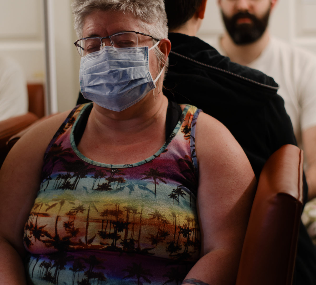 Woman in surgical mask and black rubber gloves sits to back of another woman with a man facing camera in background