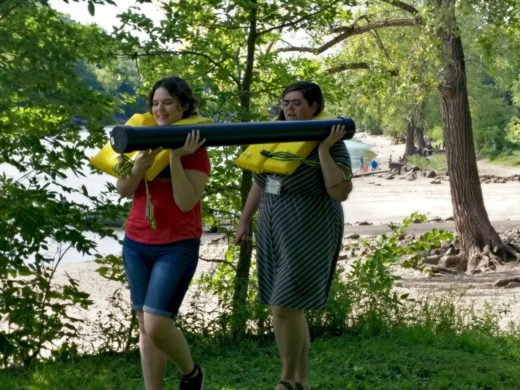 two people in lifevests carrying a long tube