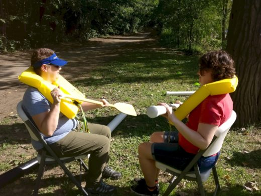two people in lifevests, simulating rowing